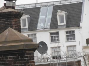 מחלון המטבח רואים דירה תחת גג מעבר לרחוב