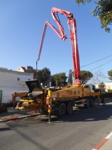 מכונה לשפיכת בטון עם רגל של חרגול ענקי מנסה להשתחל מעל לגג הבית