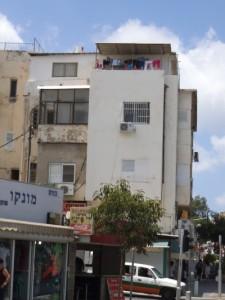 כביסה על מרפסת בנין שהיה מוזנח כנראה שיש דיירים חדשים