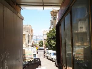 מבט בין בתים ברח' החלוץ ודרך סמטה עם הים ברקע
